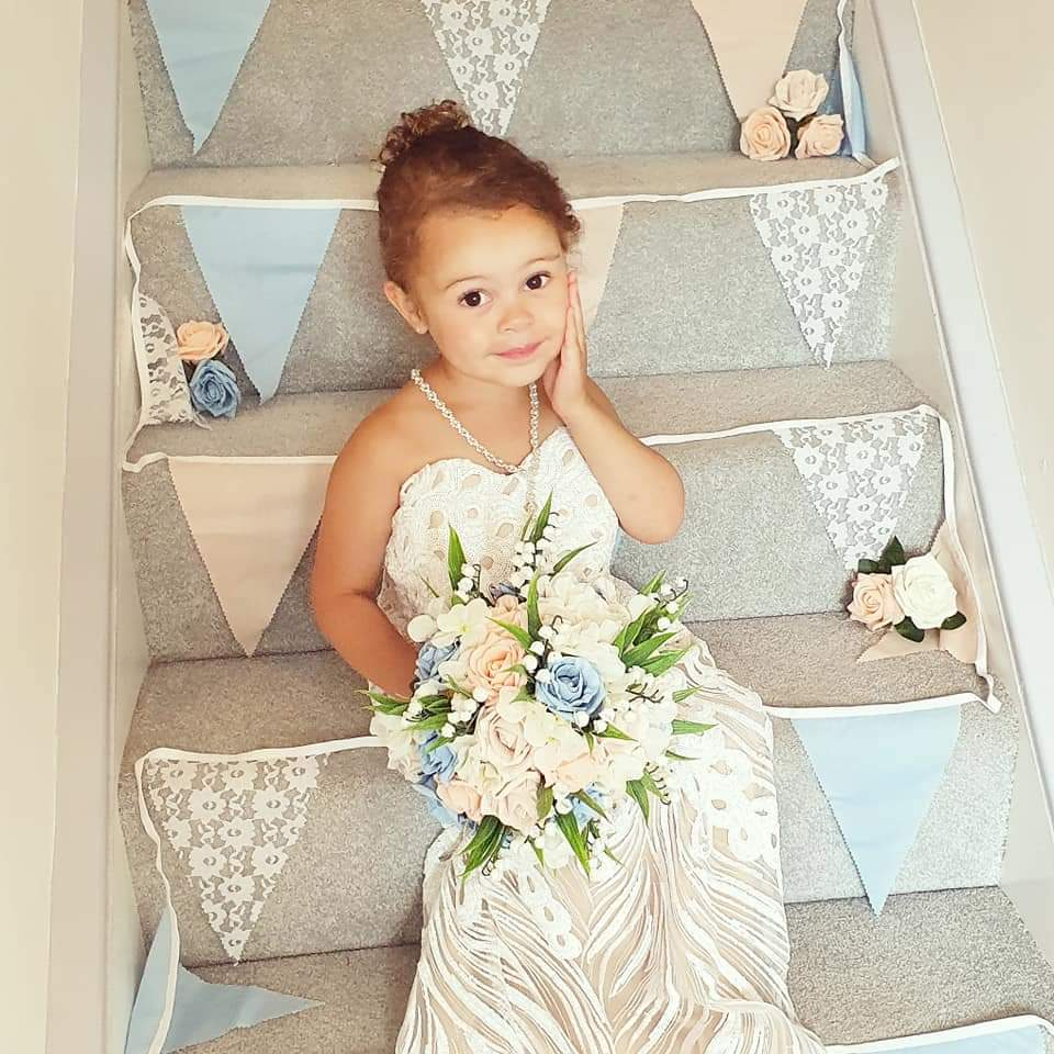 A photo of a little  girl in a wedding dress
